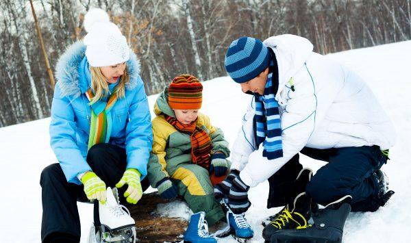 Family putting ice skates on lakeside, Scugog