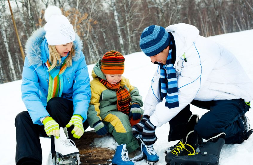 Family putting ice skates on lakeside, Scugog